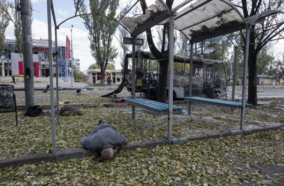 Bodies of victims killed by recent shelling lie at a bus stop near a burnt-out bus on a street in Donetsk, eastern Ukraine