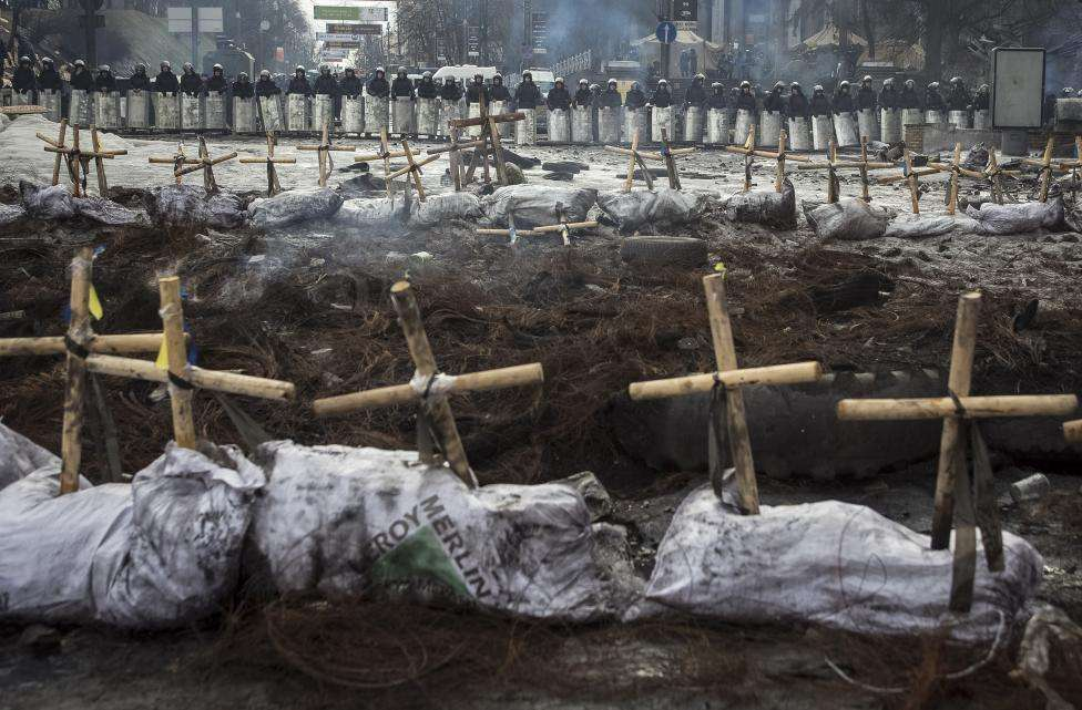Riot police stand behind crosses installed by anti-government protesters in memory of the people who have died and gone missing during clashes in Ukraine, near the barricades in Kiev