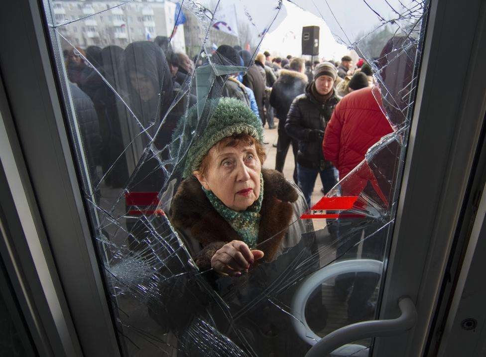 A woman looks through a damaged entrance door as pro-Russian demonstrators hold a rally outside the regional government building in Donetsk